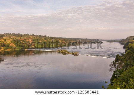 View on Victoria Nile River with rapids and island at dawn against sunrise glowing background. Jinja, Uganda, Eastern Africa. - stock photo