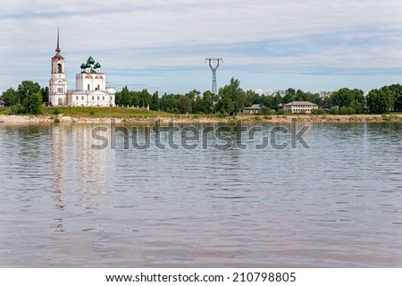 View on Vychegda River with ancient Annunciation Cathedral on riverside reflecting in water against cludy sky background. Solvychegodsk, Arkhangelsky region, Russia.  - stock photo