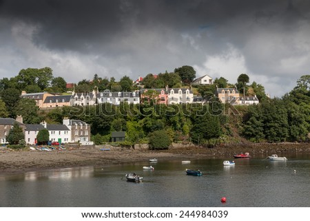 View onto Portree harbor, with ships and boats and some colorful houses, Isle of Skye, Scotland - stock photo
