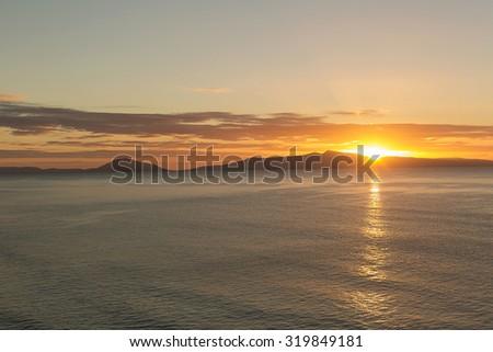 View out across the ocean of sunrise on the East Coast of Tasmania, Australia - stock photo