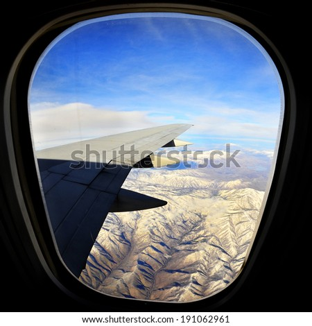 View out of airplane window at wing, sky and ground below while traveling - stock photo