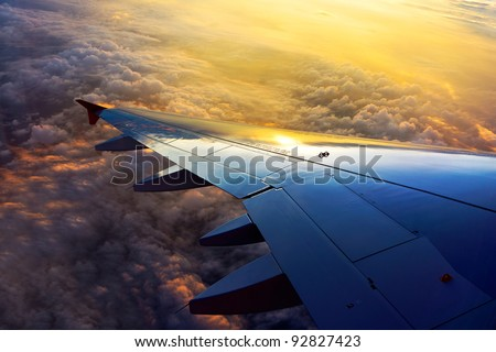 View out of airplane wing in flight Morning golden light below the clouds - stock photo