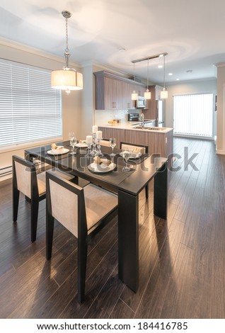 View, outlook, panorama at luxury living site. Nicely decorated dining table and the kitchen at the back. Interior design of a brand new house. Vertical.