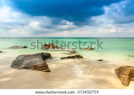 view over a tropical beach with granite rocks, white sand and a turquoise indian ocean under a blue sky - stock photo