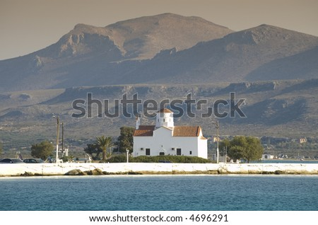 View over antique white church on the island and mountain background - stock photo