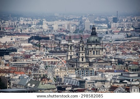 view over cupola of basilica of saint istvan and over ferris wheel situated in historical center of budapest. - stock photo