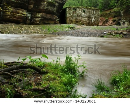View over dark mountain river with high water level after heavy rains to ruin of stony water mill. - stock photo