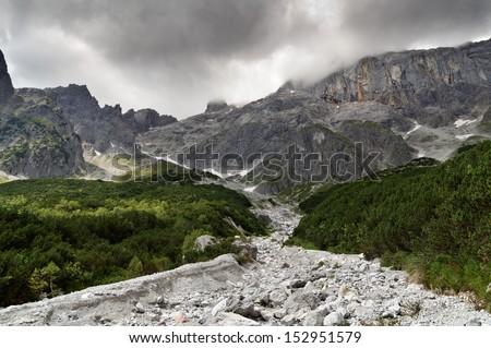 view over detritus and mountain pines at Birgkar under a dark sky, mountain Hochkoenig, Salzburg, Austria - stock photo