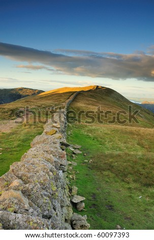 View over dry stone wall towards late evening light on Birkhouse Moor, English Lake District - stock photo