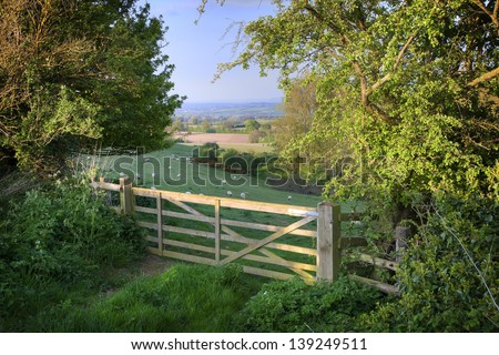 View over farm gate towards pretty English countryside - stock photo