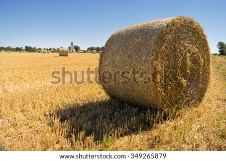 View over harvested fields in late summer to the church of Gardby on the island of Oland, Sweden. In the foreground a straw bale ready for transport.