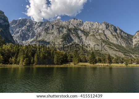 view over koenigssee to Watzmann from sun illuminated mountain massif, impressive white cloudscape over the mountain chain with bright blue sky, shore line with trees - stock photo