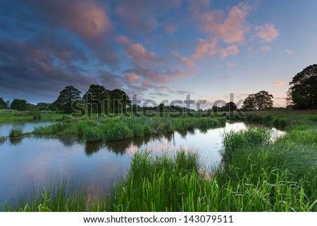 View over meandering stream in green landscape - stock photo