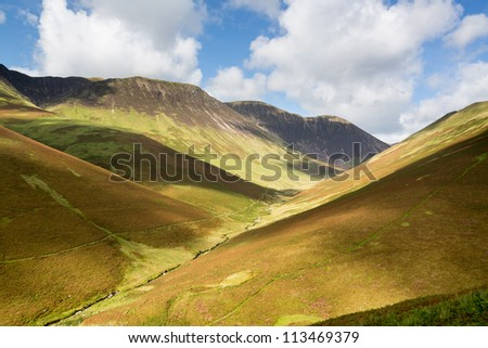 View over Newlands Valley from pass showing steep sided mountains and hills in English Lake District - stock photo