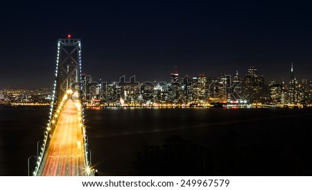 View over San Francisco bay bridge and skyline at night - stock photo