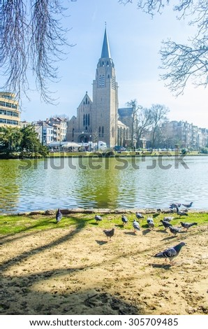 View over the artificial pond situated next to the flagey square in belgian brussels, where local citizens go to relax when sunny. - stock photo