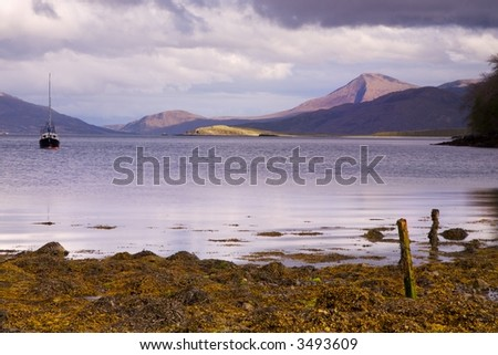 View over the calm evening waters of loch Sligachan on the isle of skye. Dusk light hits the edges of the distant mountain range and a single sailing boat is moored in the foreground. - stock photo
