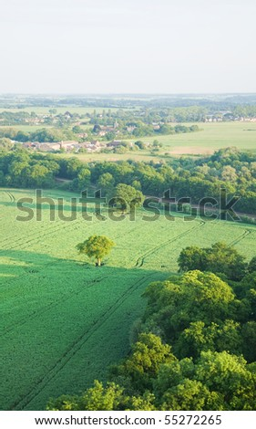 view over the early summer green fields and a small village from the air; East Anglia; UK - stock photo