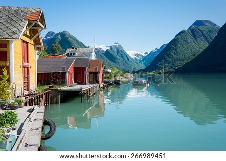 View over the fjord Fjaerlandsfjord and the village of Mundal (or Fjaerland) with some snow-capped mountains, a boat, reflection in the water and yellow and red boathouses in Sogn of Fjordane, Norway. - stock photo