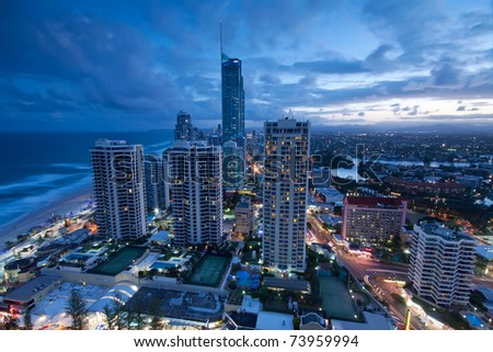 view over the modern city at dusk with ocean beside (gold coast,queensland,australia) - stock photo