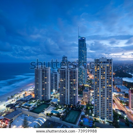 view over the modern city at dusk with ocean beside on square format (gold coast,queensland,australia) - stock photo