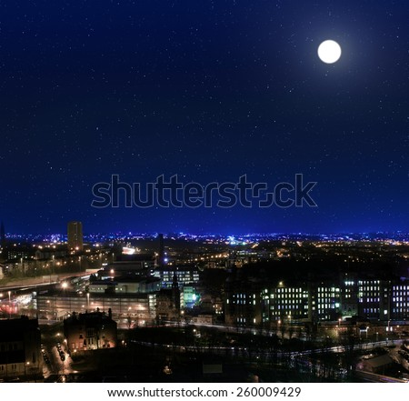 View over the rooftops towards Glasgow Royal Infirmary at night - stock photo