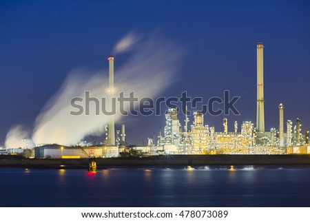 View over the Scheldt river in Antwerp, Belgium to a large oil refinery with night blue sky, illumination and steam.