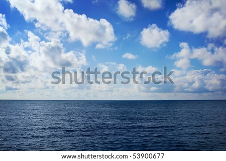 view over the sea far below, white clouds - stock photo