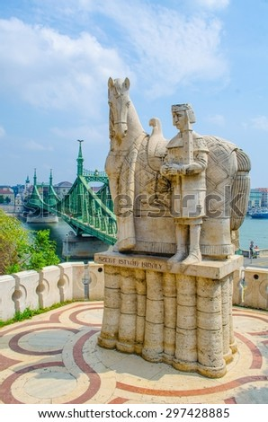 View over the statue of saint gellert situated on gellert hegy hill with szabadsag bridge behind. - stock photo