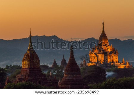 View over the temples of Bagan in Myanmar to the surrounding mountains at sunset - stock photo