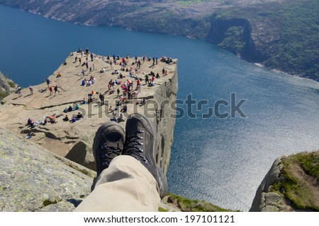 View over the world famous Preikestolen - or pulpit rock - over the Lysefjord, Norway, with hiking boots in the foreground - stock photo