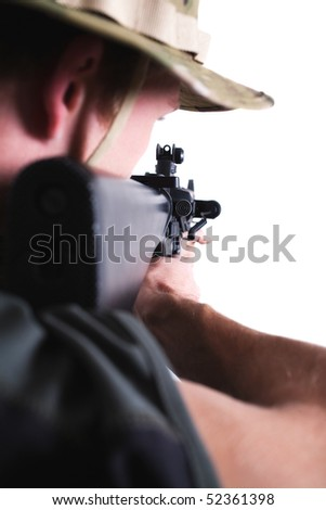 View over young soldier's shoulder shooting with M16 assault rifle.
