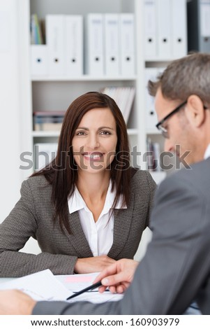 View past the shoulder of a businessman consulting paperwork to a smiling beautiful businesswoman in a meeting - stock photo