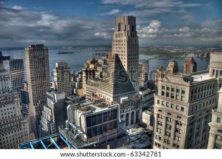 View south from Wall Street at high altitude. Visible over the many tall buildings in lower Manhattan is the Statue of Liberty and New York Harbor. - stock photo