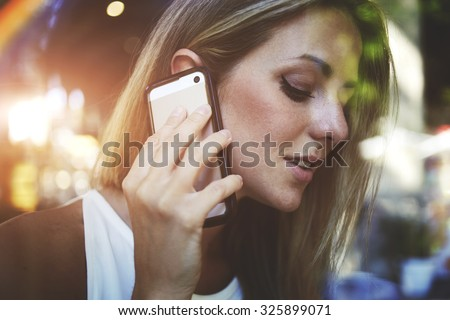View though the window of successful businesswoman talking on mobile phone with her partners while sitting in cafe during work break, beautiful woman having cell telephone conversation in coffee shop - stock photo