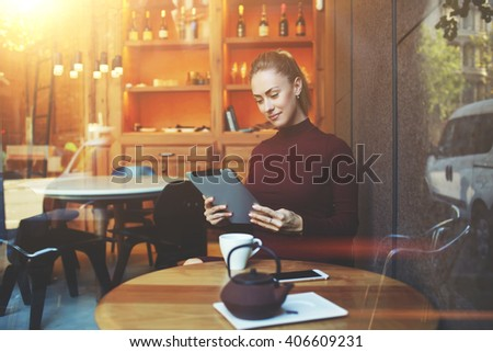 View though the window of woman reading electronic book on digital tablet during lunch break in comfortable cafe inside,pretty female freelancer work on touch pad while sitting in modern coffee shop  - stock photo