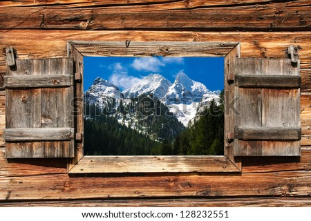 View through a wooden window on a mountain panorama with forest in foreground - stock photo