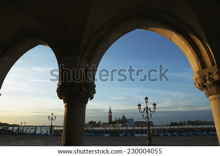 View through an archway over Venice harbor with the San Giorgio Monastery in the background, Venice, Italy - stock photo