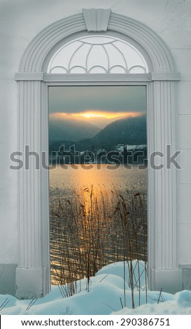 view through arched door, sunset at wintry lake in the alps - stock photo