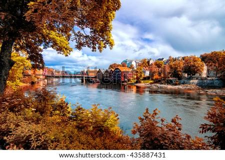 View through autumn foliage to Nidelva river, Trondheim city, Norway - stock photo