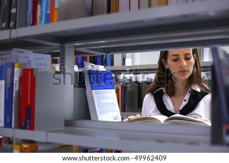 View through bookshelf at attractive student standing in between bookshelves in modern university library reading a book. - stock photo