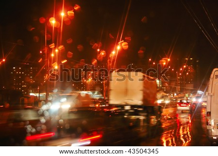View through car windshield to night road with moving cars. Autumn, rain, reflections. - stock photo
