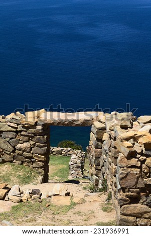 View through door frame of Chinkana archeological site of Tiwanaku origin on Isla del Sol (Island of the Sun) on Lake Titicaca in Bolivia (Selective Focus, Focus on the door frame and beyond) - stock photo