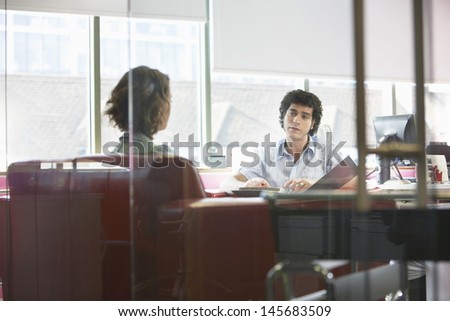 View through glass wall of businessman and woman in meeting - stock photo