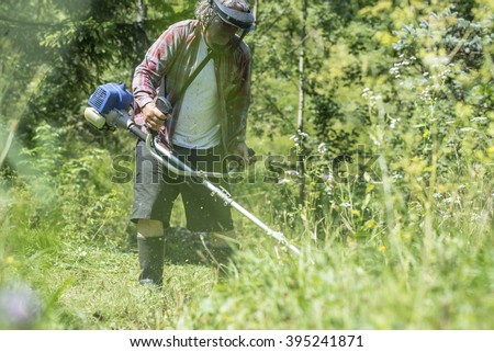 View through high grass of a man with protective head-wear and goggles trimming the lawn with weed eater.