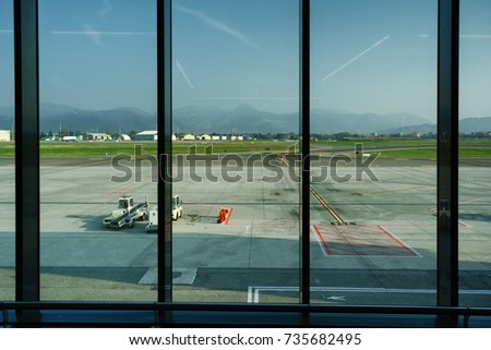 View through the airport departure terminal window to the runway, town buildings and misty mountains near the horizon