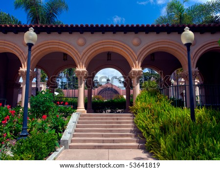 View through the arches of Casa de Balboa building in Balboa Park in San Diego to Botanical Building - stock photo