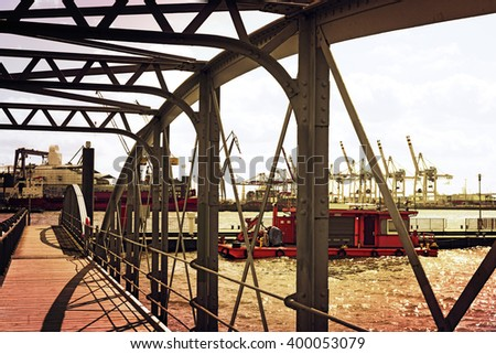 View through the bridge of Hamburg Fischmarkt to the container harbor. Toned image in the stfernoon sun. Sunset at the Hamburg harbor. - stock photo