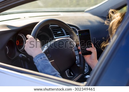 View through the open side window from behind of an anonymous woman driving her car as she reads an sms or text message on her mobile phone, blank screen visible - stock photo