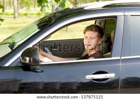 View through the open side window of a smiling handsome young man driving a car in countryside - stock photo